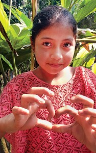 After watching Indiana linemen climb poles and string wire in her village, a Guatemalan girl forms a heart with her fingers as an expression of gratitude toward the Americans who came to change their lives. Photo by Diane Willis