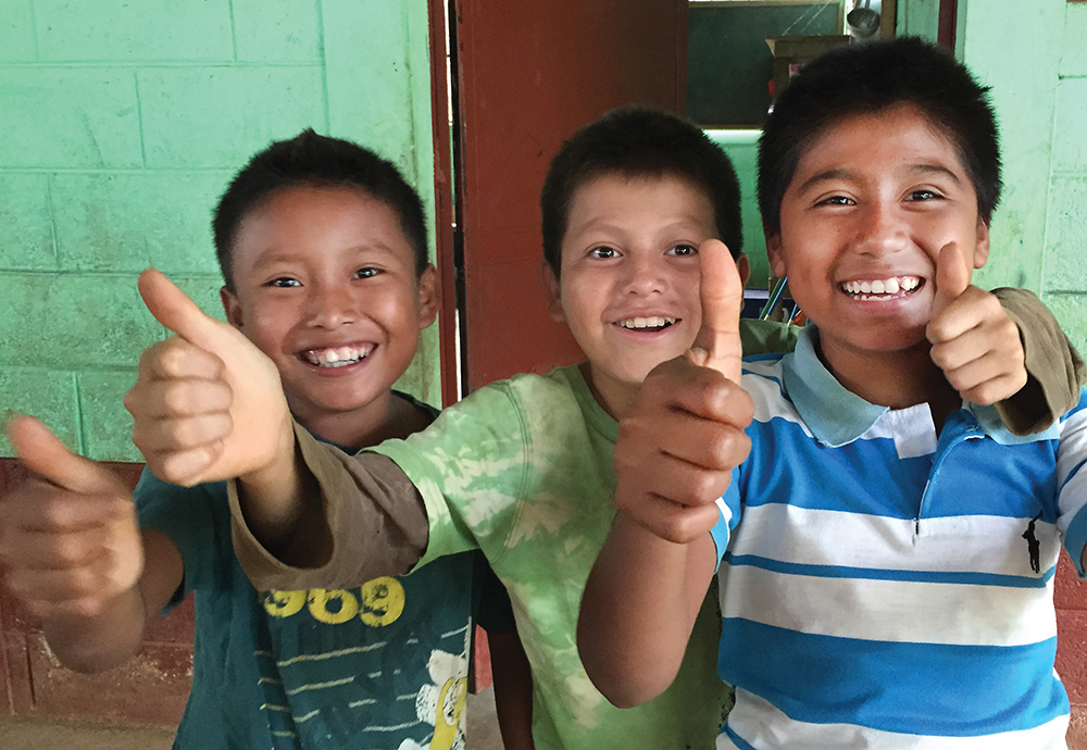 "After the power lines were built and energized, field testing was done the day before the official ""inauguration day."" The moment the lightbulbs came on in their classroom during a field test, village boys celebrate with a thumbs up and cries of ""La luz! La luz."" (""The light! The light."") Linemen said their proudest moment was seeing the joy on the faces of the children."