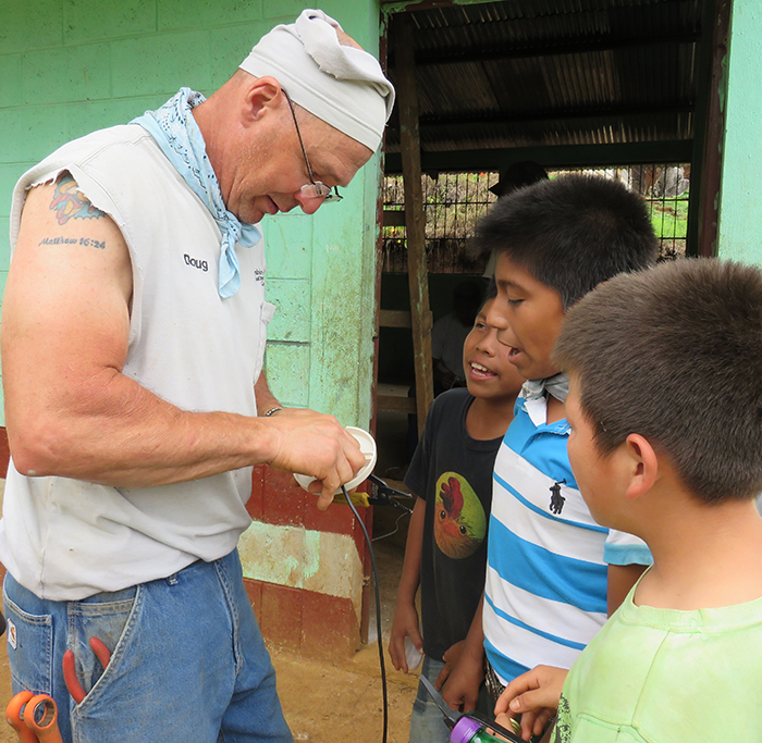 Doug MacLain, Marshall County REMC, shows boys in the village how to wire a light socket.