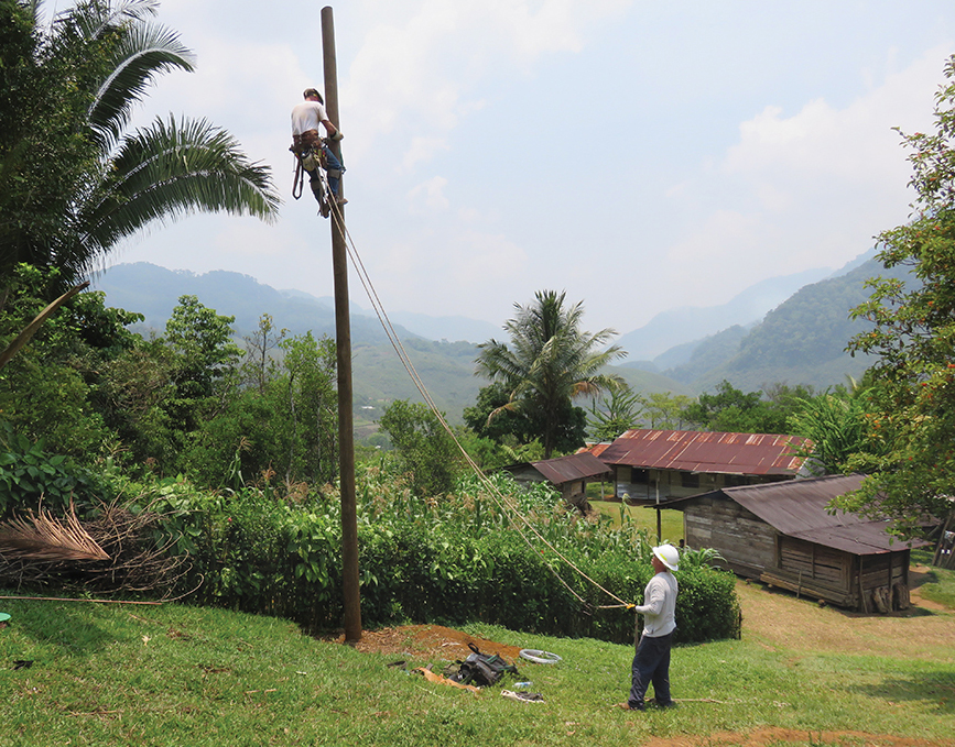 In the remote and rugged beauty of northeastern Guatemala, Hoosier lineworkers Brian AmRhein, from Decatur County REMC, on pole, and Doug MacLain, from Marshall County REMC, prepare to install the hardware on the pole to bring electricity to these village buildings. Photo by Scott Sikora, Kankakee Valley REMC