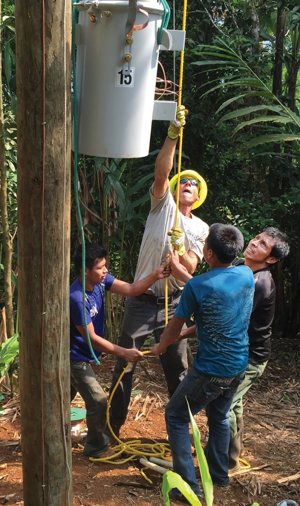 Pat Scheurich, of Jasper County REMC, gets some assistance from local men hoisting a transformer to the top of a pole. The Indiana linemen said the villagers' work ethic, pride and commitment amazed them. Photo by Diane Willis