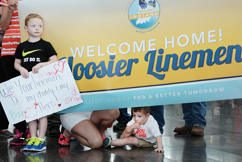 Scores of family and co-op co-workers greeted the linemen as they arrived at Indianapolis International Airport with signs, hugs and kisses after the two-week trip. Among those anxiously waiting for the group to emerge beyond the security gates are Lukas Shirley, left, and his little brother, Gunner, sons of Boone REMC lineman Michael Shirley. Photo by Richard G. Biever