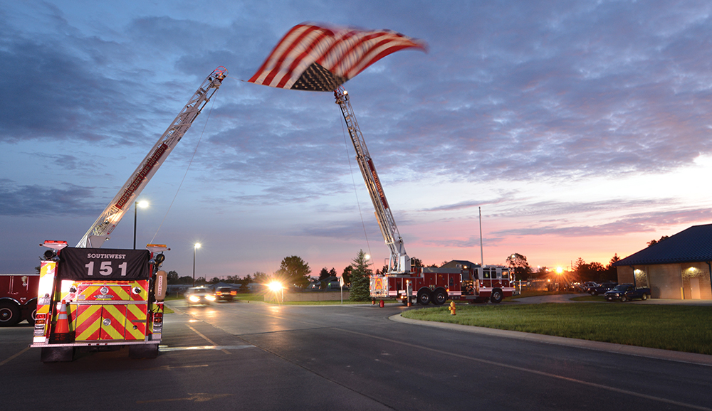 5:55 am: Honor Flight participants arrive at the 122nd Fighter Wing Air National Guard Base in Fort Wayne May 20 to begin their day, passing under a large flag hoisted by the Southwest Allen County Fire District.