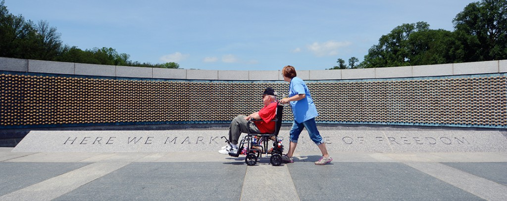 """11:44 am: Passing the """"Freedom Wall"""" at the WWII memorial is veteran Wayne Lambert and guardian, daughter Jan Pyle. As the inscription reads, the stars """"mark the price of freedom."""" Over 4,000 gold stars, each representing 100 U.S. military deaths in the war, make up the wall. A tour guide noted to the group that if the World War II Memorial had been designed like the Vietnam Veterans Memorial as a wall with the name of each casualty inscribed, the WWII wall would have to have been nine times larger than the Vietnam memorial."""