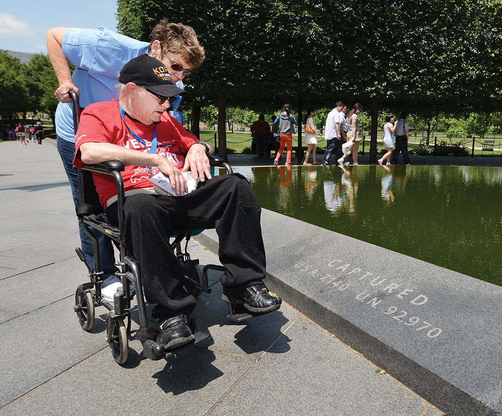 """1:19 pm: Raymond Turpen, one of the two Korean War veterans on the Honor Flight, and his guardian, Sue Gipson, pause before the Pool of Remembrance at the Korean War Veterans Memorial. At their feet, the memorial notes the numbered captured, """"U.S.A. 7,140."""" Turpen was visibly touched; he was one of those 7,140 during the war that was waged from June 1950 to July 1953."""