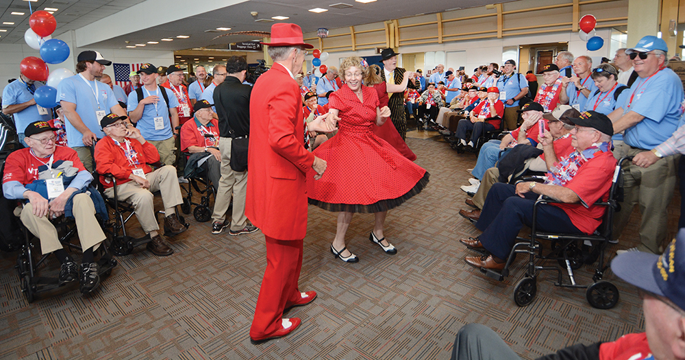 6:38 pm: Returning to Reagan National Airport for the flight home, the group is met with more kisses and hugs and entertainers dressed in zoot suits and dresses of the 1940s who danced the jitterbug and more. They rolled with veterans in wheel chairs and danced with others.