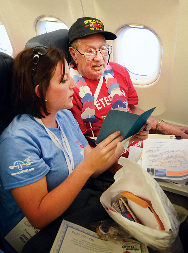 8:33 pm: Homeward bound, Honor Flight volunteers spring one more surprise on the veterans and guardians — mail call! A part of every Honor Flight, bundles of thank you letters and cards — many of which are personalized — are delivered to each veteran. At right, Jade Hill reads one of the cards to her grandfather, Wendell Stapleton.