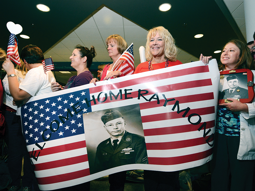 9:41 pm: (above) Inside the airport terminal, an estimated 2,000 people create a corridor of cheering, flag waving, applauding and handshaking supporters stretching from the arrival gate to the exit doors. A group of family and friends wait for Honor Flight participant Raymond Turpen to make his way through the well wishers.