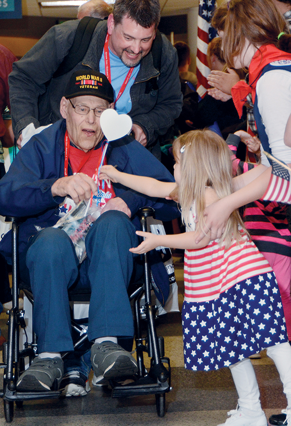 10:09 pm: In a scene repeated from the day's beginning, veteran Charles Krause is handed a red, white and blue heart from one of many children greeting the returning flight. His guardian, grandson Marty Krause Jr., looks on.