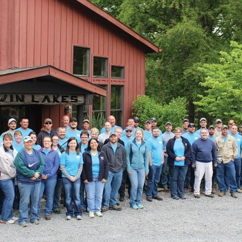 Tipmont staff members pose outside a red barn at Twin Lakes Camp.