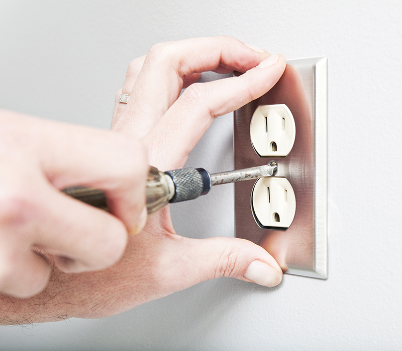 Hands installing electrical outlet cover plate.