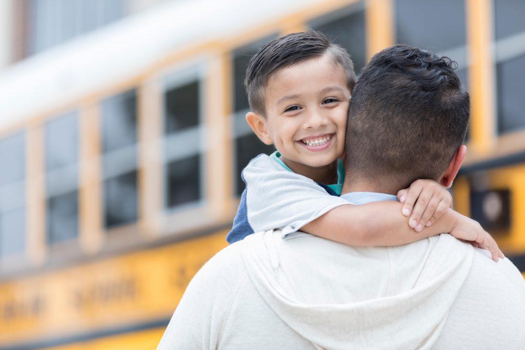 Boy getting read for school with dad