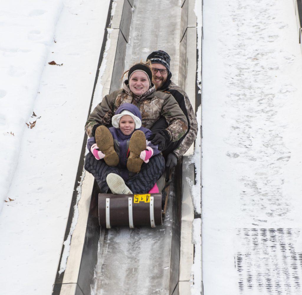 Family sliding down toboggan run at Pokagon State Park