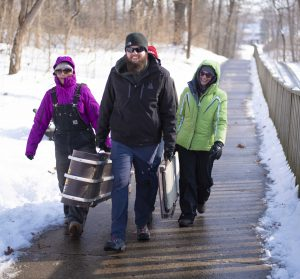 Group carrying toboggans in winter weather gear.