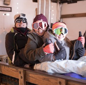 Family in winter weather clothing and giving a thumbs up before toboggan run