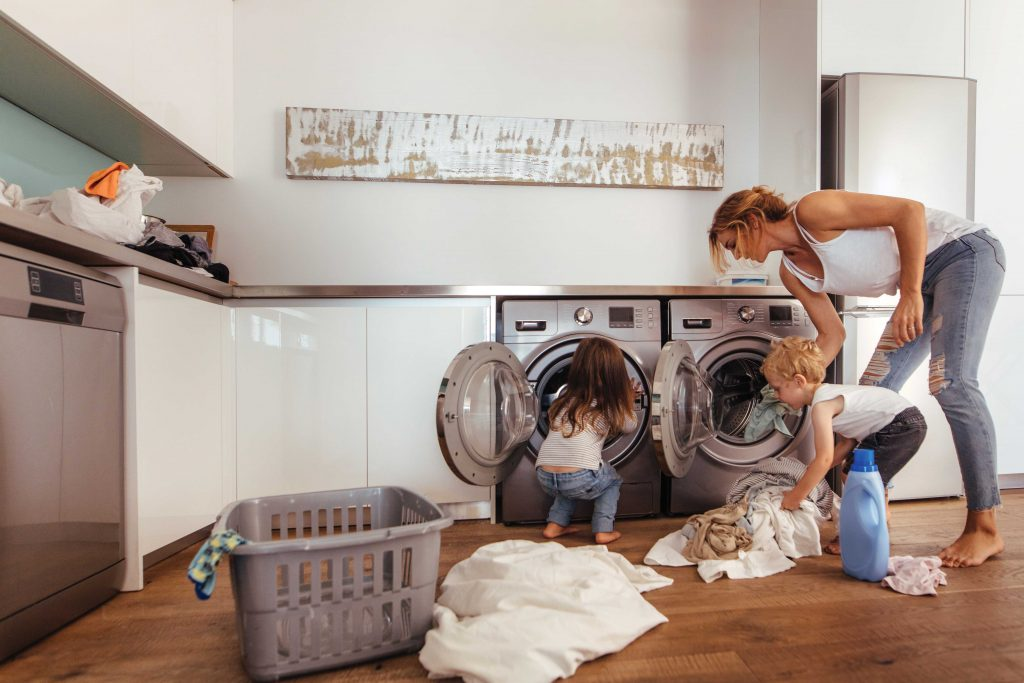 Woman doing laundry with children