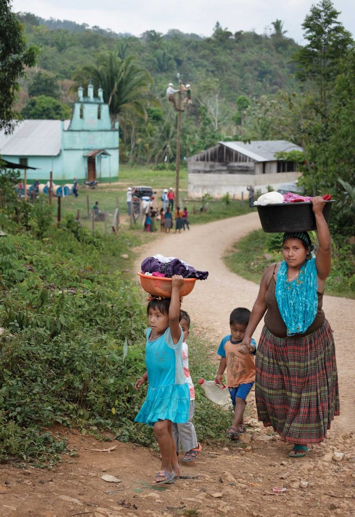 Guatemalan woman and family carrying supplies to their home on their heads.