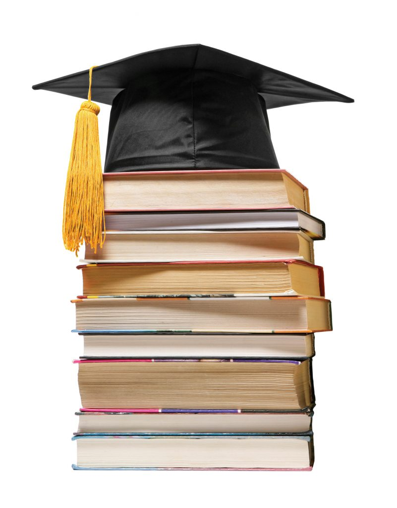 Photo of graduation cap on top of books