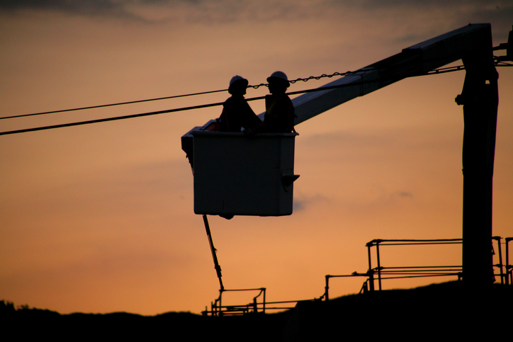 Two men in a bucket lift working on power lines