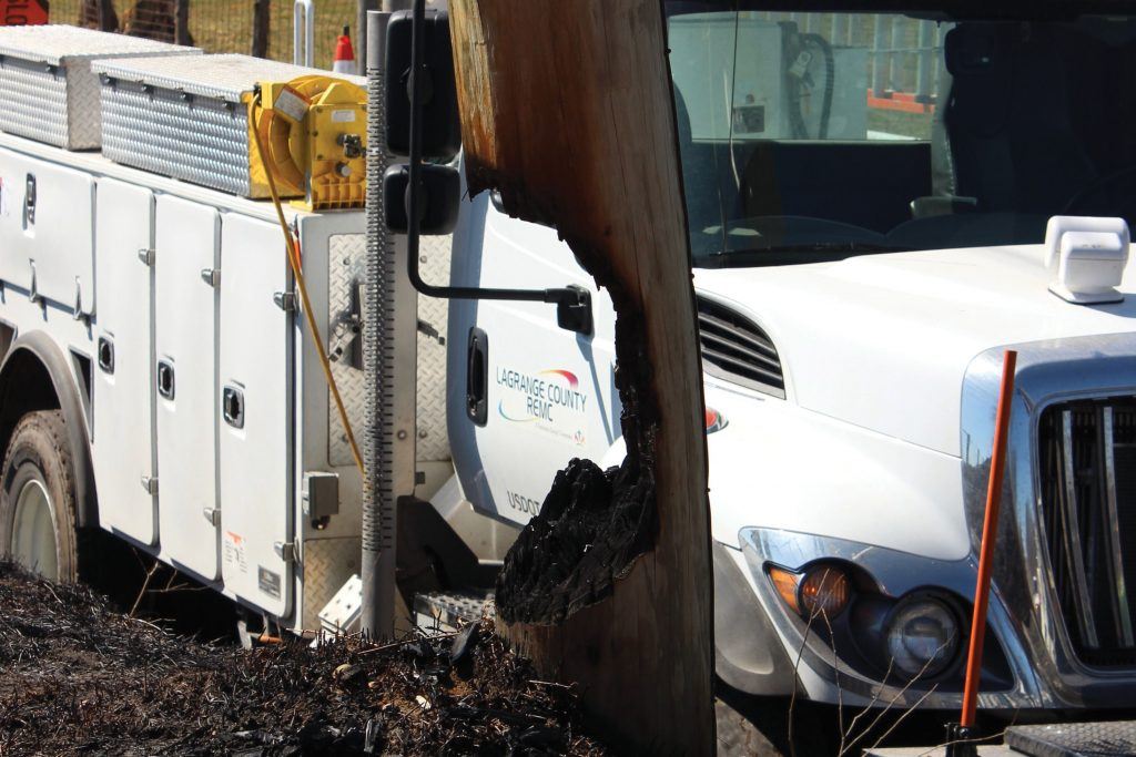 Picture of burnt pole in front of utility truck