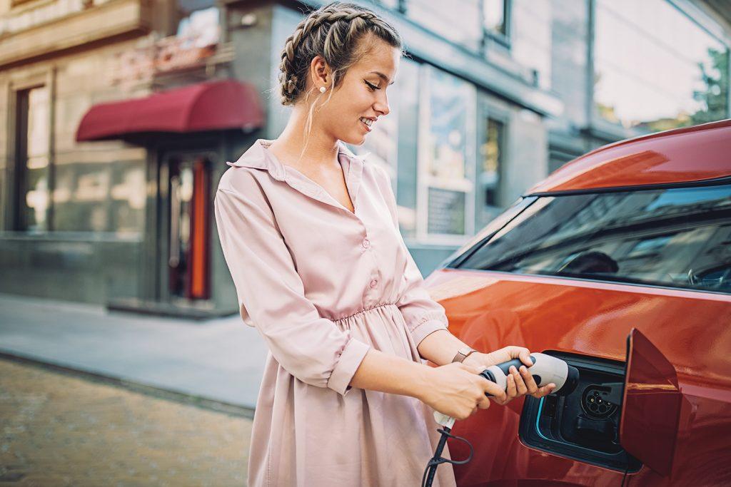 Woman plugging in electric car