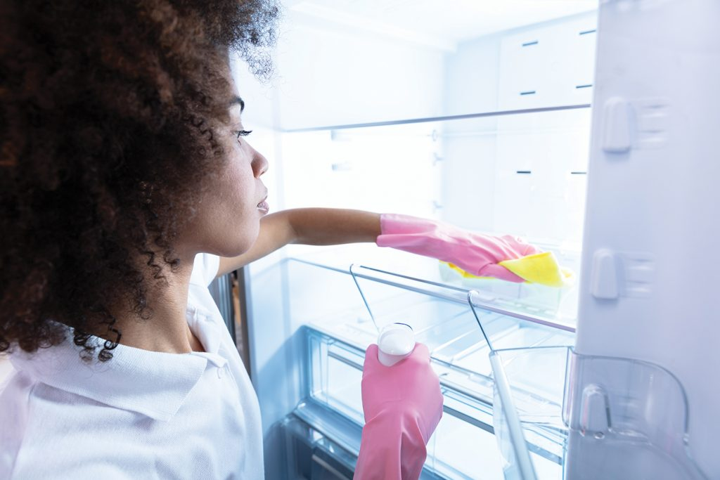 Woman cleaning refridgerator