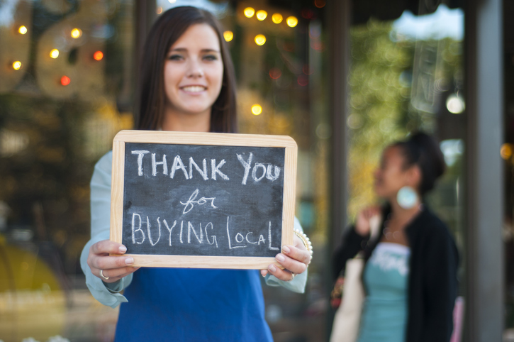 Woman holding buy local sign