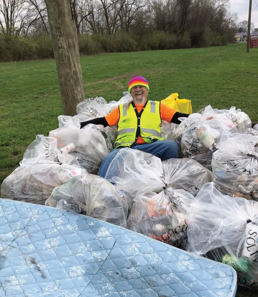 Man surrounded by trash bags.
