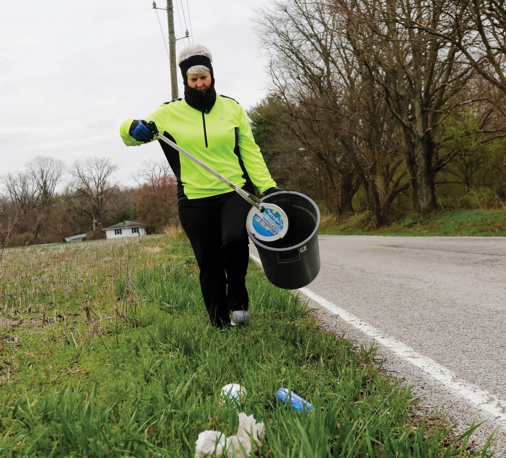 Photo of someone picking up trash along a roadside