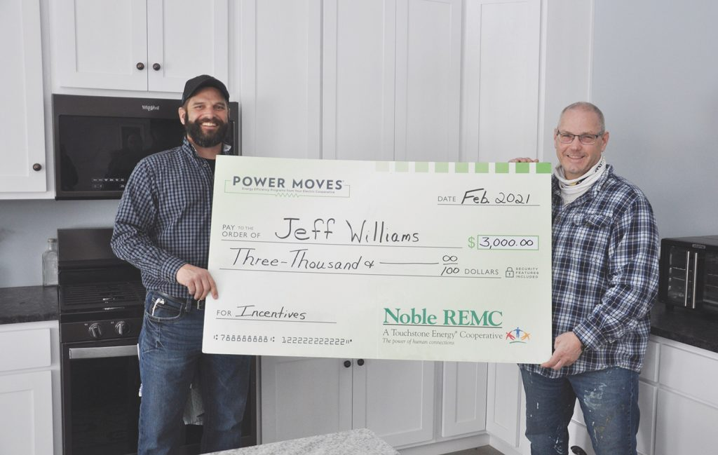 Noble REMC Energy Advisor Brian Hawk, left, presents a Power Moves incentives check to homeowner Jeff Williams.