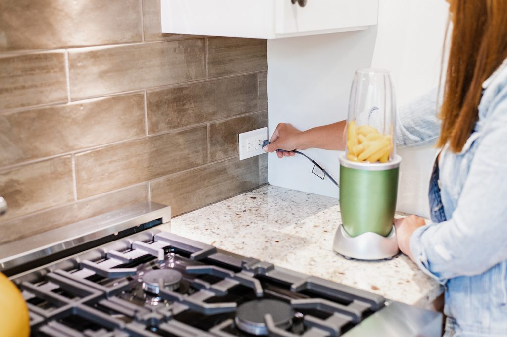 Woman plugging an appliance into a receptacle