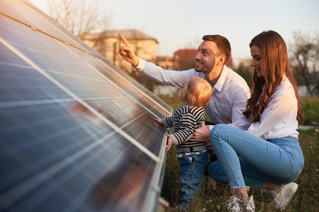 Family next to solar panel