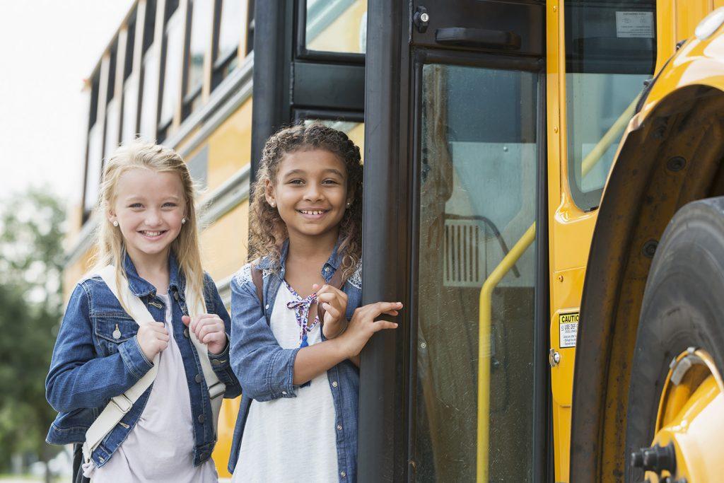 Girls getting on a school bus