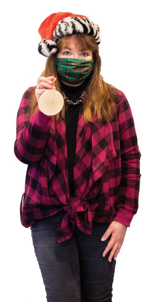 Em in mask holding Christmas ornament